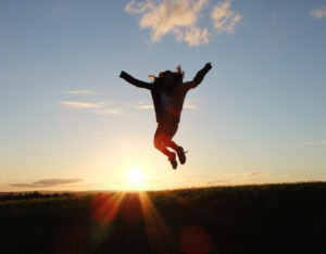 A girl jumping in her arms raised in silhouette photography