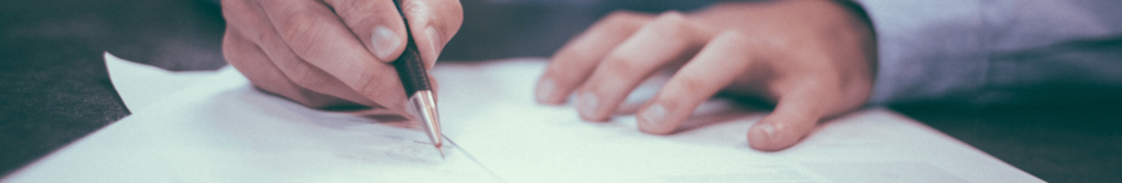 A photo of man's hands holding a pen signing the papers