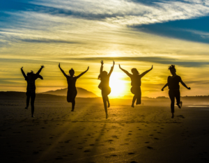 5 girls jumping and raising their arms in silhouette photography